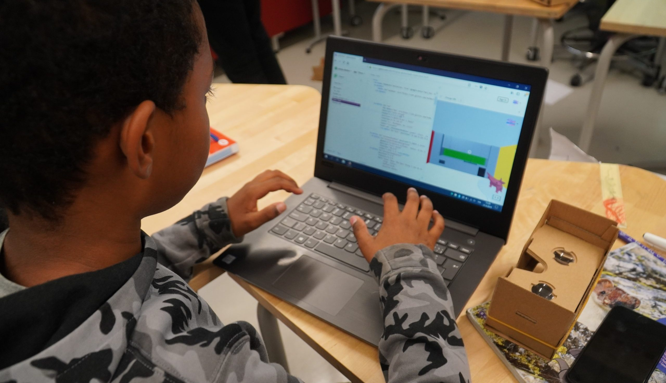 Oppilas kokeilee tietokoneella koodin muokkaamista, pöydällä virtuaalitodellisuuslasit