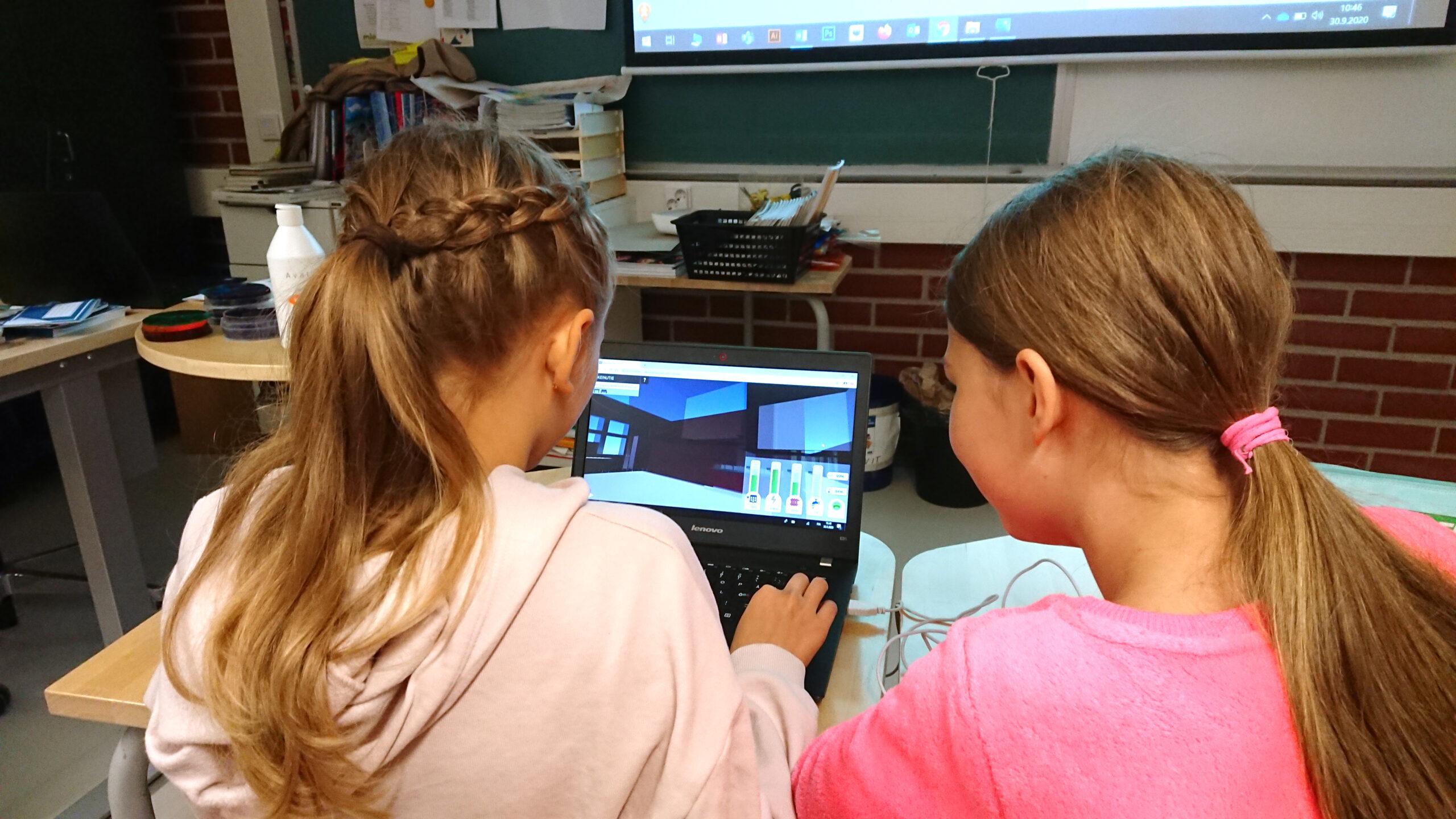 Kaksi oppilasta tietokoneella kokeilemassa Playsignin digitaalista kaksosta heidän koulustaan